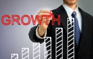 Businessman writing growth over a rising bar graph